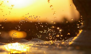 water-surge-wave-sea-foam-sprays-drops-at-sunset-sky-sun-glare-night
